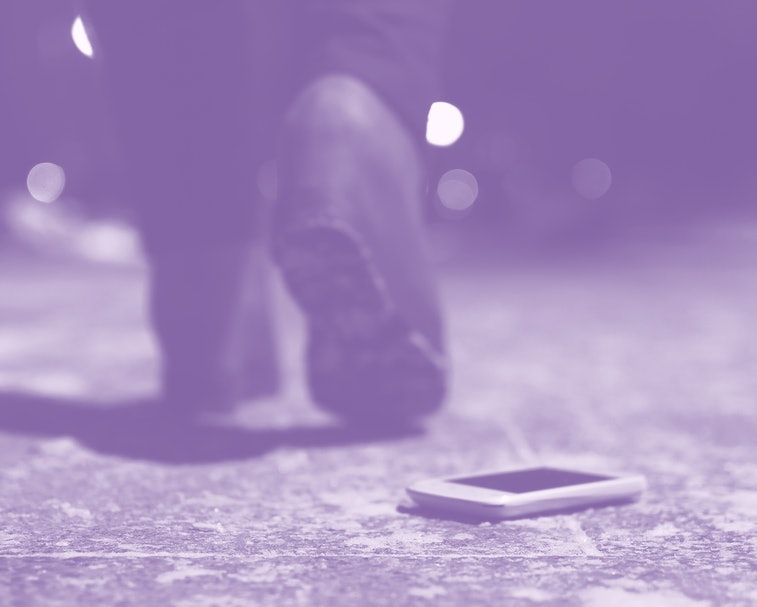 Lost mobile phone dropped from a woman pocket on the night footpath and is walking away silhouette of woman.