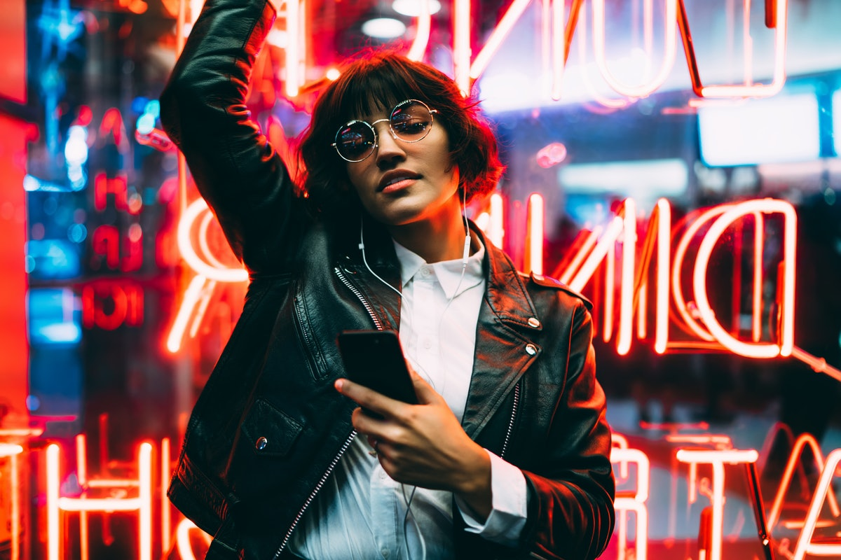 A woman in a leather jacket and sunglasses, dances in front of a neon sign while holding her phone.