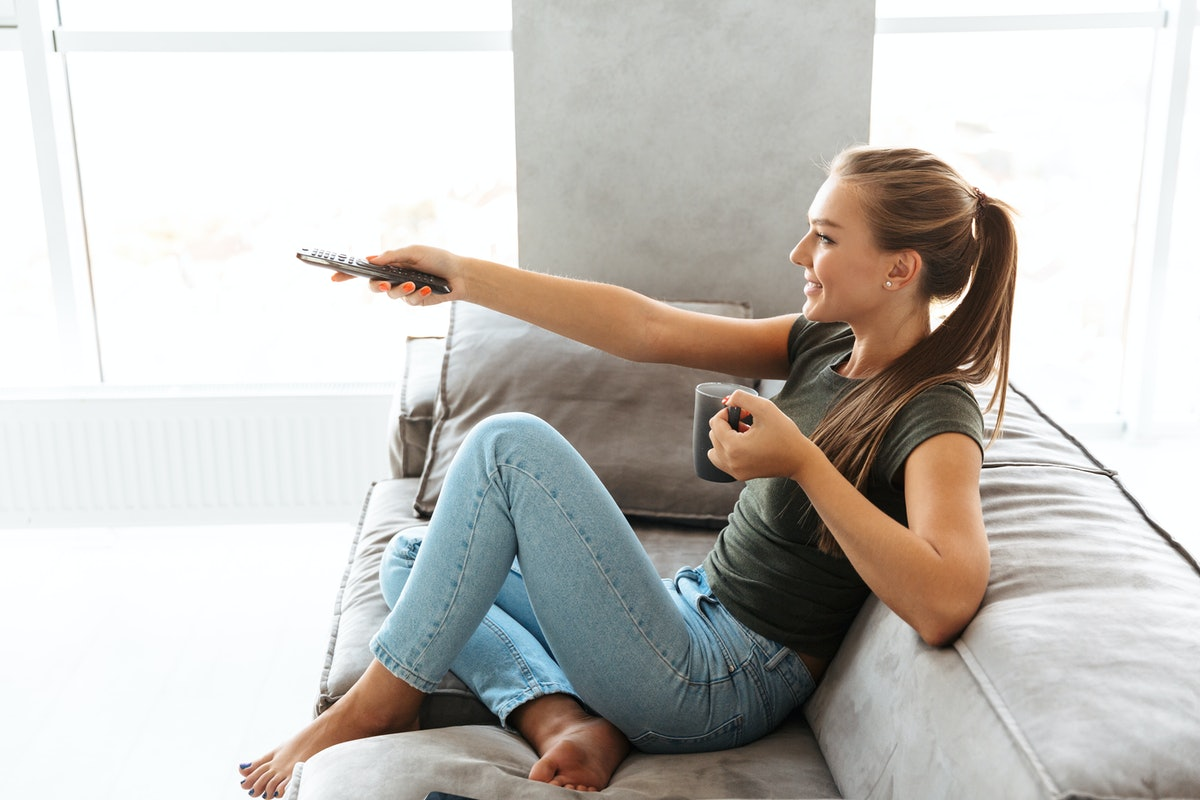 Cheerful young woman sitting on a couch at home, changing channels, drinking tea from a cup