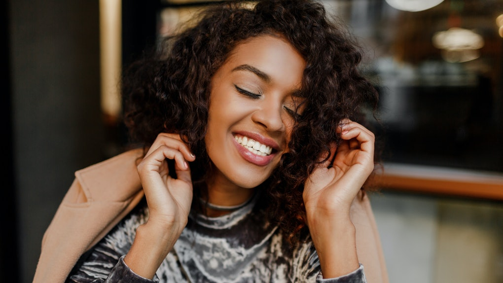 Close up lifestyle portrait of happy carefree black woman enjoying coffee break in Paris. Wearing elegant velvet dress. Perfect white teeth. Curly hairs.