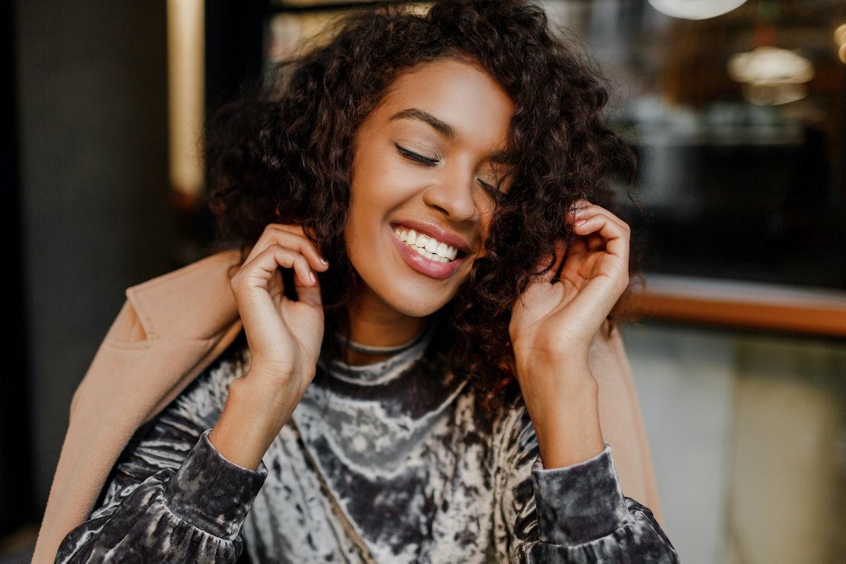 Close up lifestyle portrait of happy carefree black woman enjoying coffee break in Paris. Wearing elegant velvet dress. Perfect white teeth. Curly hairs.