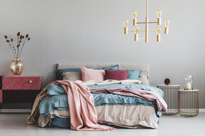 Flowers in stylish glass vase on diy velvet covered pastel pink and burgundy nightstand next to warm bed with blue and beige bedding and pink pillows