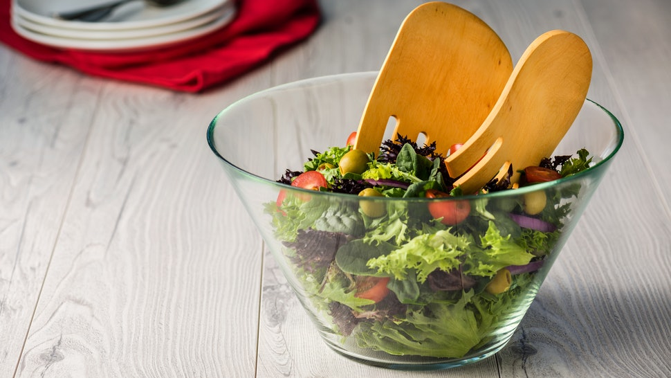 Green salad in glass bowl on a grey rustic table
