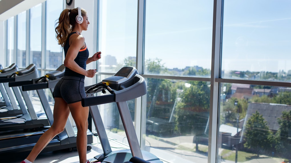 A woman runs on a treadmill in a gym that has big windows.