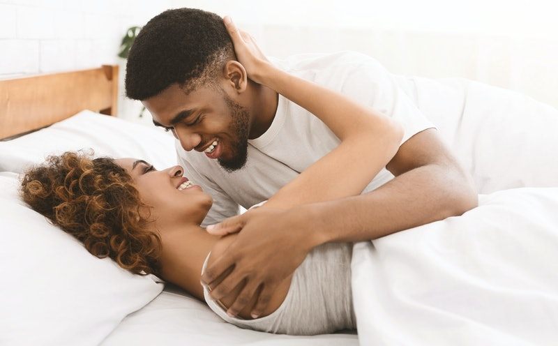 Happy loving african-american couple relaxing on bed at home, enjoying togetherness and tenderness in love, copy space