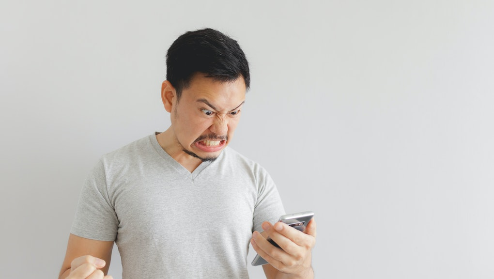 Angry Asian man in grey t-shirt get mad on the smartphone.