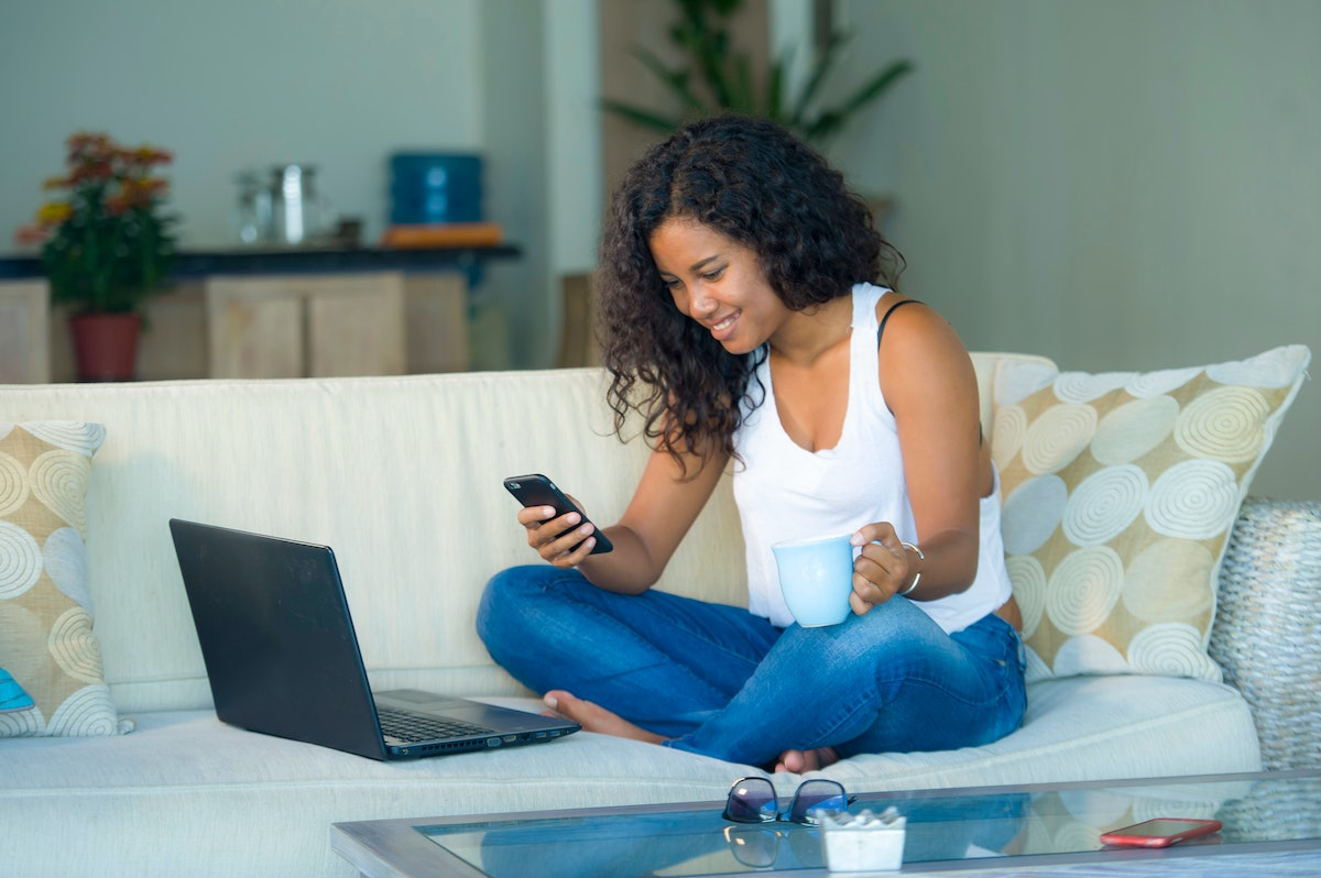 lifestyle portrait of young happy and beautiful black afro American woman using internet texting on ...