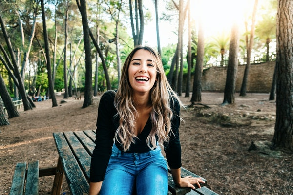 Beautiful teenage girl laughing out loud full of life and happiness when leaving high school.