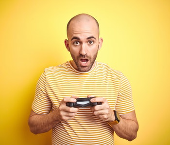 Young man playing video games using joystick gamepad over isolated yellow background scared in shock with a surprise face, afraid and excited with fear expression