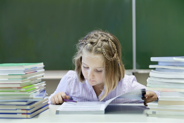 Model Released - Schoolgirl, 7 years, reading a book whilst sitting between two stacks of books, in front of a blackboard