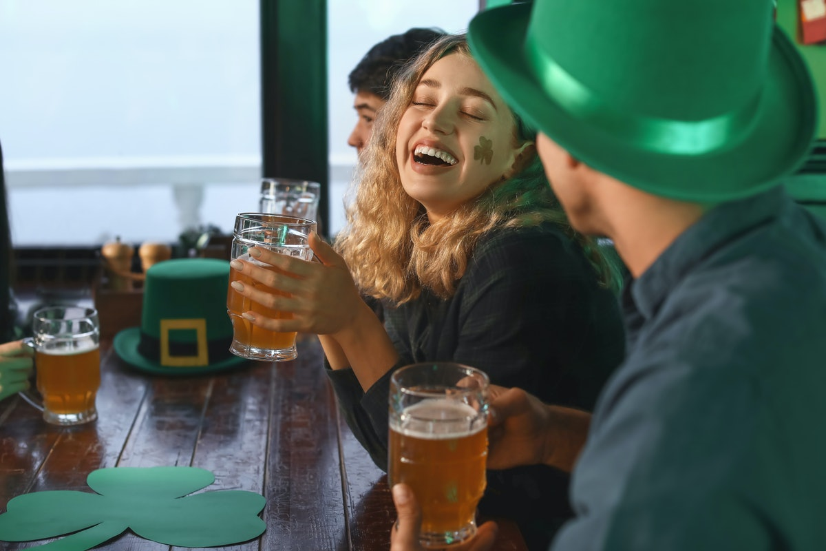 A woman with a shamrock sticker on her cheek laughs while celebrating St. Patrick's Day with friends...