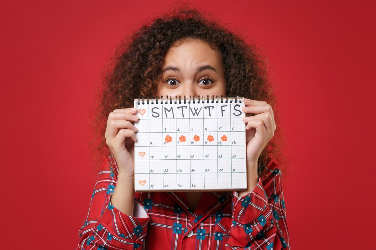 African american girl in pajamas homewear posing rest at home isolated on red background. Relax good mood lifestyle concept. Covering face with female periods calendar for checking menstruation days