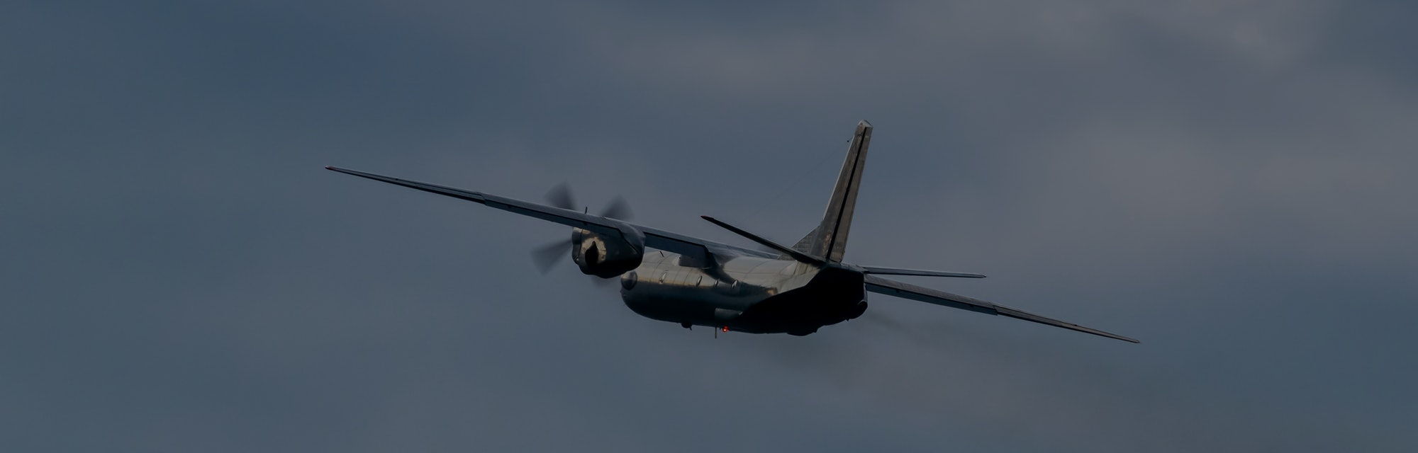 Turboprop cargo plane is rolling after takeoff on stormy sunset