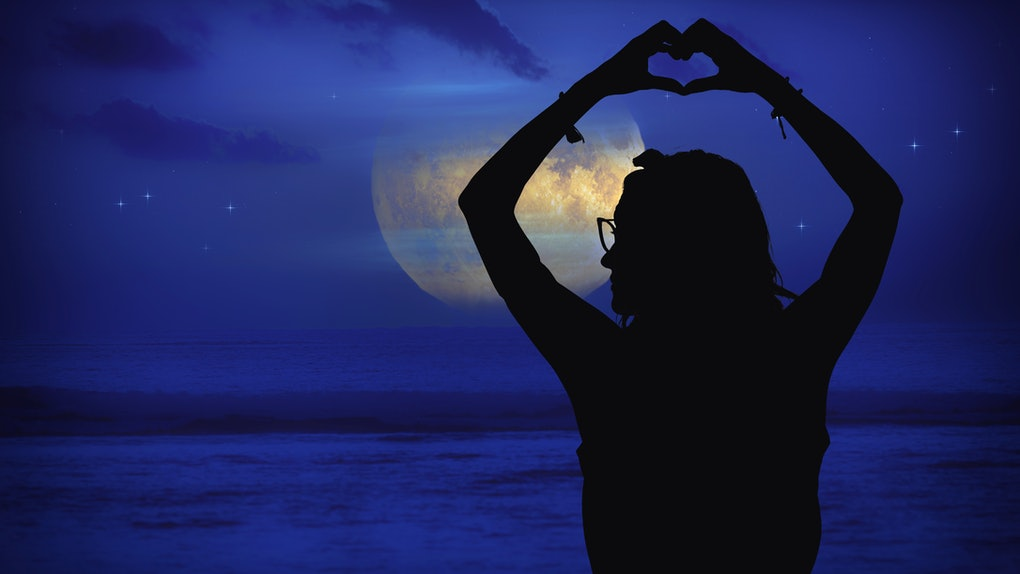 Silhouette of a girl at moonlit sky with stars near ocean holding heart - shape sign with hands. My astronomy work.