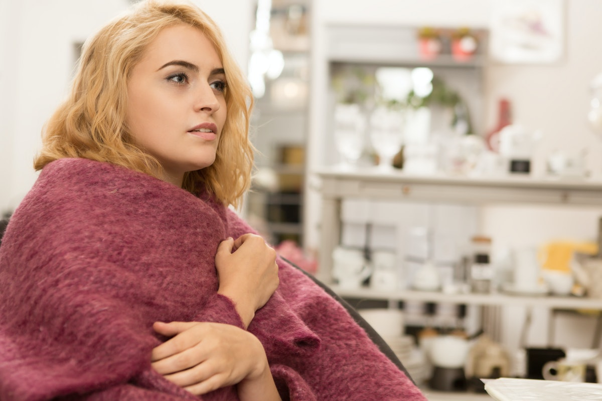 Beautiful young woman relaxing at home sitting wrapped in warm pink blanket looking away thoughtfully copyspace enjoyment lifestyle leisure weekend living coziness seasonal femininity sensuality