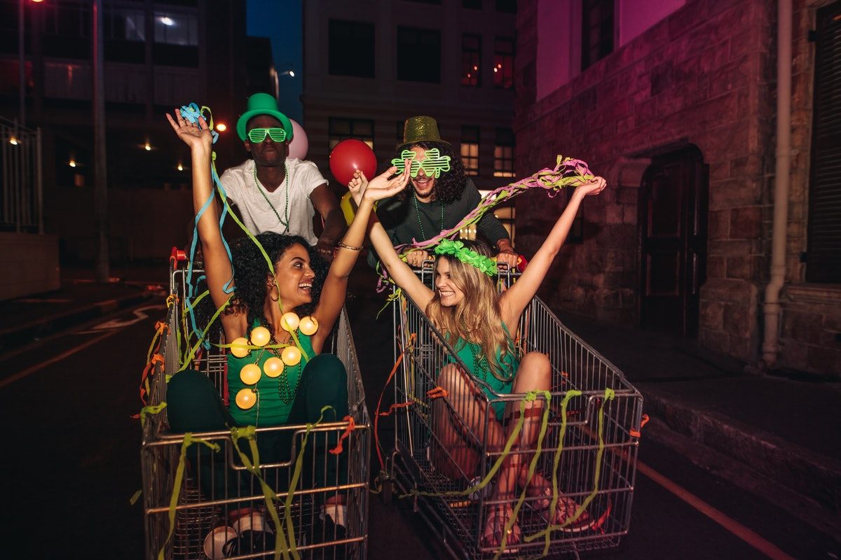 Four friends have fun on St. Patrick's Day in shopping carts and throw streamers in the air.