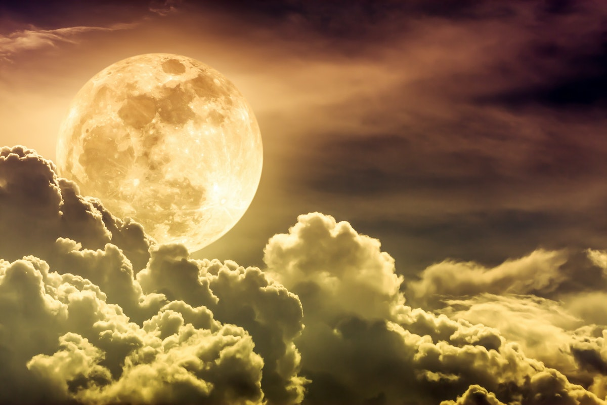 Attractive photo of gold background nighttime sky with clouds and bright full moon with shiny. Night...