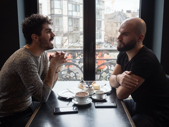 Two young guys friends with beards arguing in a coffee shop