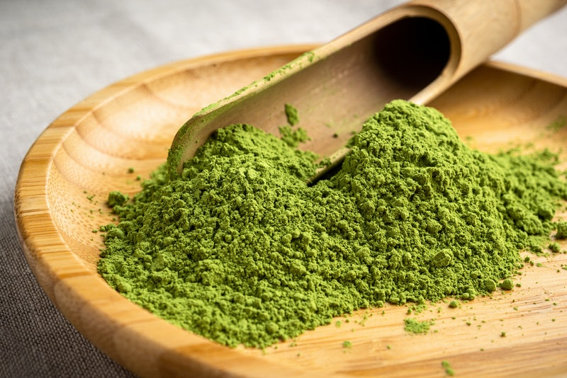 Powder matcha in a bamboo bowl with spoon on a woven linen background,close up