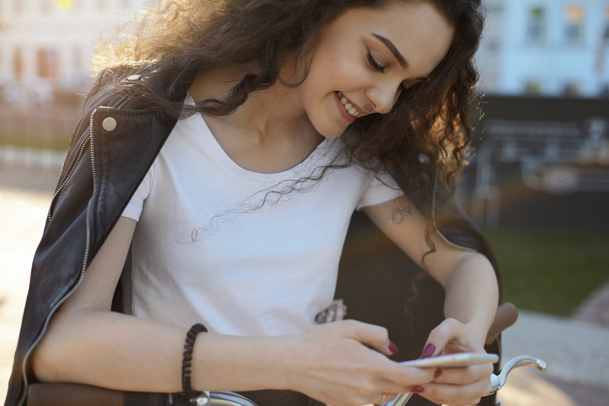 Cropped outdoor shot of pretty girl with charming shy smile reading romantic text message from her boyfriend or browsing pictures on her social networks accounts, enjoying online communication