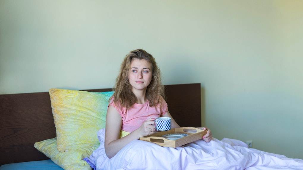 A woman relaxes with a cup of coffee in bed.