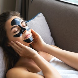 Young beautiful woman is relaxing at home with applied black peel-off mask on her face