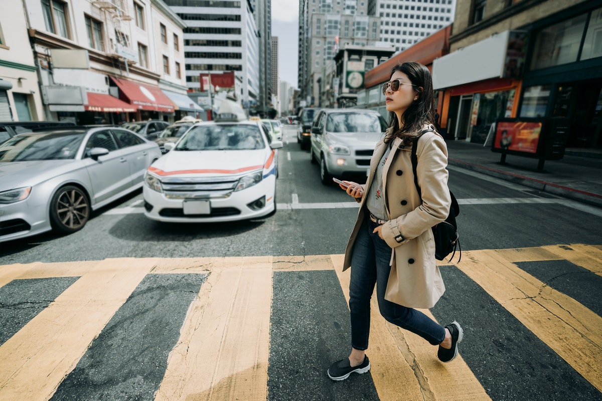 full length of young asian office lady walking on zebra cross going to work. girl backpacker holding cell phone searching online map in busy city urban. cars vehicle waiting stop traffic light