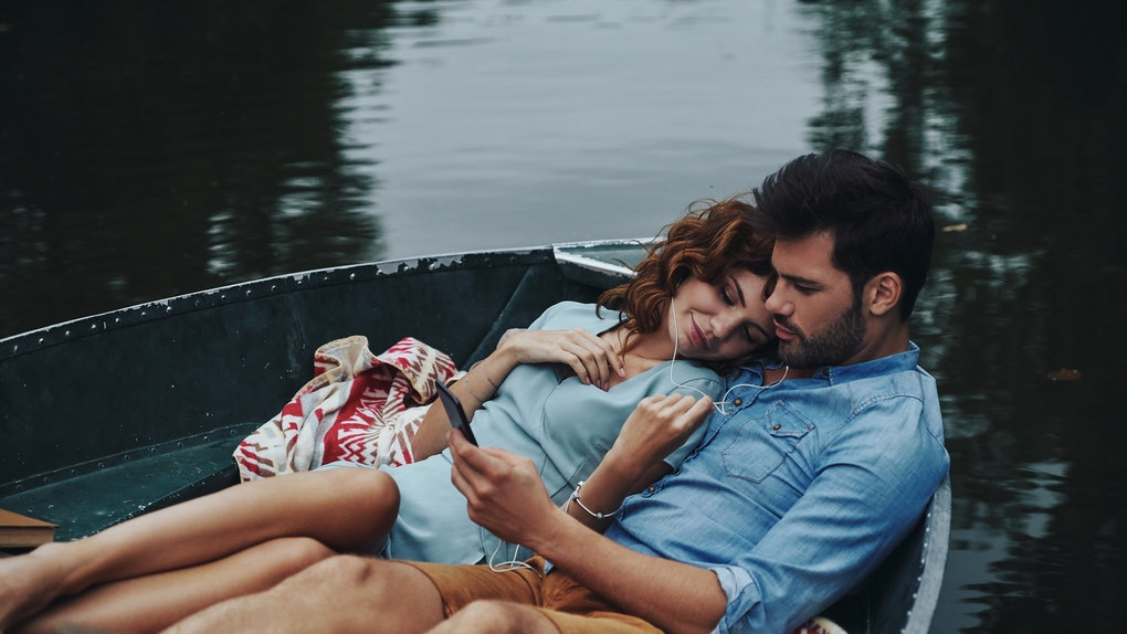 A couple relaxes in a rowboat, listening to music.