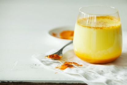 Healthy ayurvedic drink golden almond milk or pumpkin turmeric latte with curcuma powder on white ba...