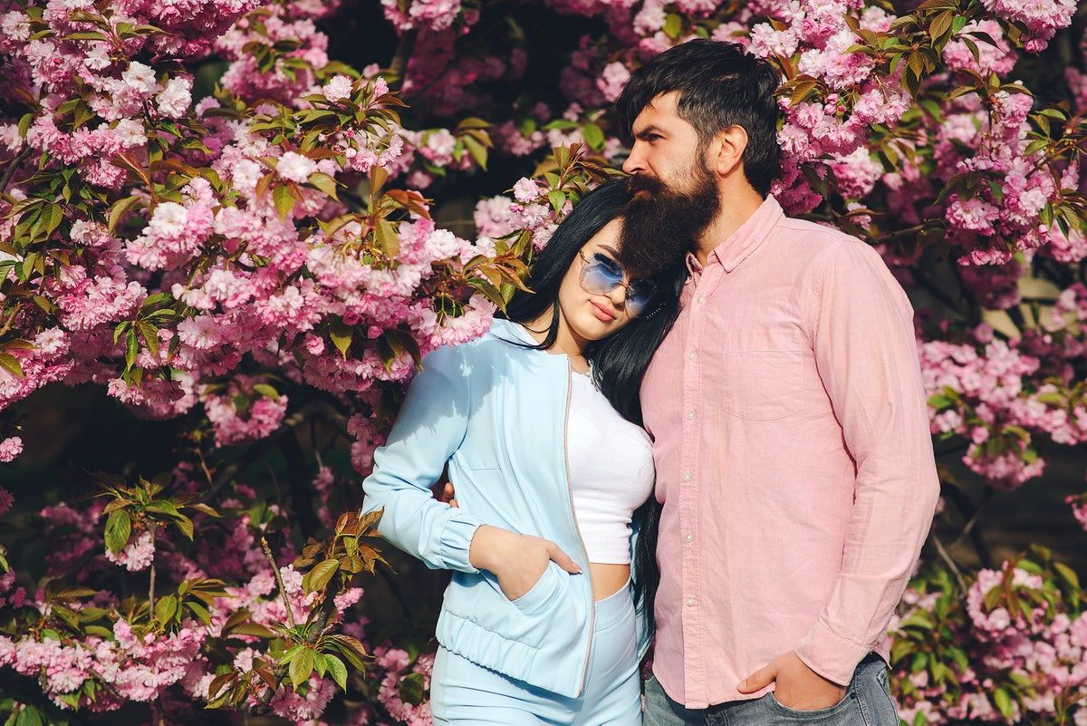 A woman wearing all blue holds onto her partner in pink, while standing in front of spring cherry blossoms.