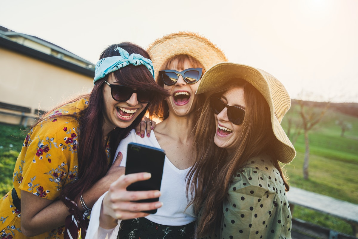 Happy millennials girls laughing and messaging on a smartphone outdoor. Three women having fun smiling taking a photo with their cell phone.