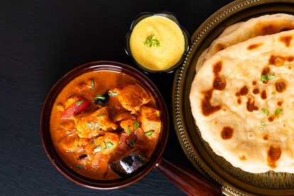 Food concept homemade Tandoori Chicken Masala curry with naan bread and yogurt dipping sauce with co...
