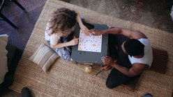 Top view of multiracial couple sitting on floor and playing board game. Woman throws dice, takes car...