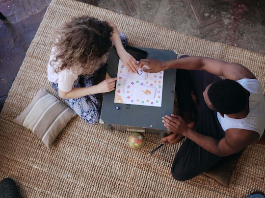 Top view of multiracial couple sitting on floor and playing board game. Woman throws dice, takes card. Man waits turn.