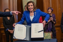 Democratic Speaker of the House Nancy Pelosi reacts after she enrolled the Coronavirus Aid, Relief, ...
