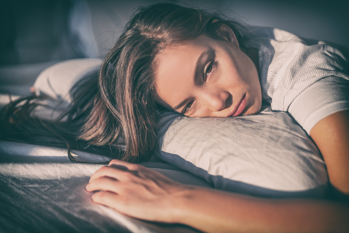 Tired woman lying in bed can't sleep late at night with insomnia. Asian girl with funny face sick or sad depressed sleeping at home.