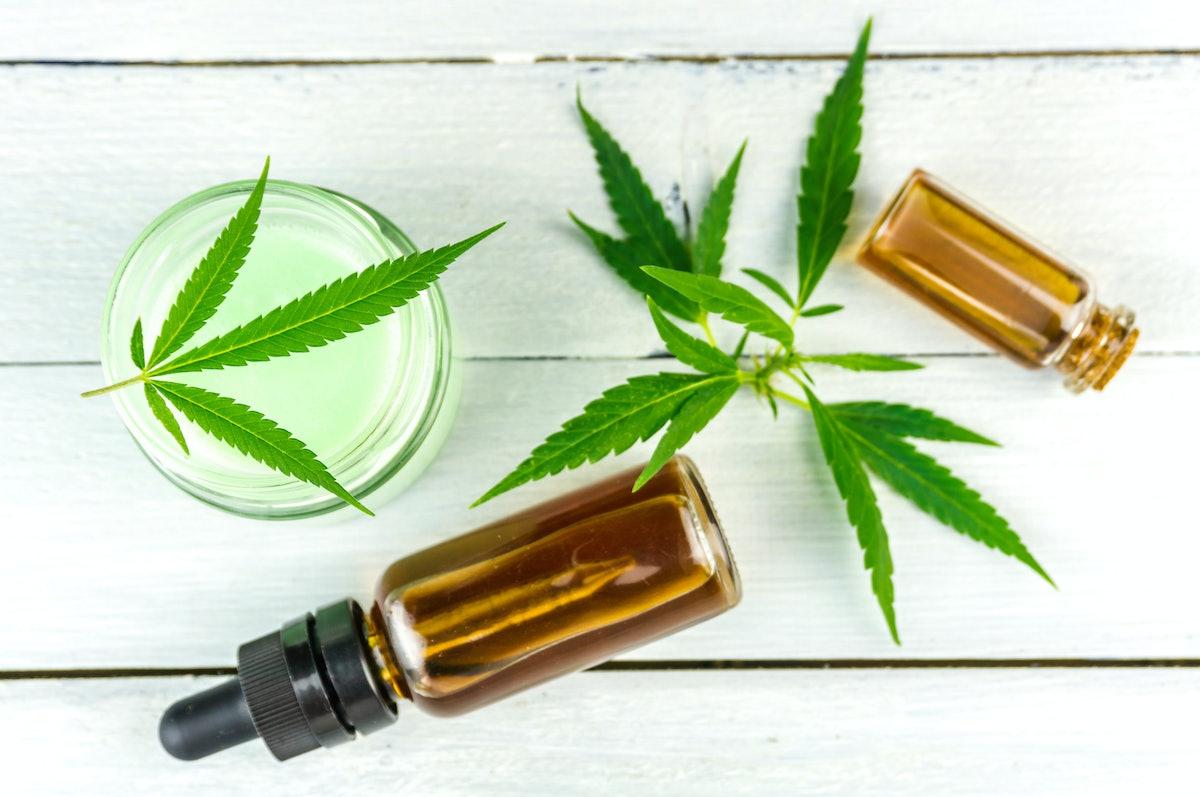 CBD Cannabis Hemp topical cream and oils balm with cannabis leafs on wooden table