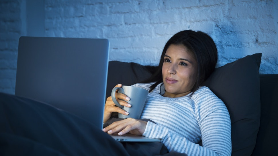 young beautiful hispanic woman in pajamas on bed at home bedroom working happy with laptop computer late at night or using the internet chat and social network in technology addiction concept