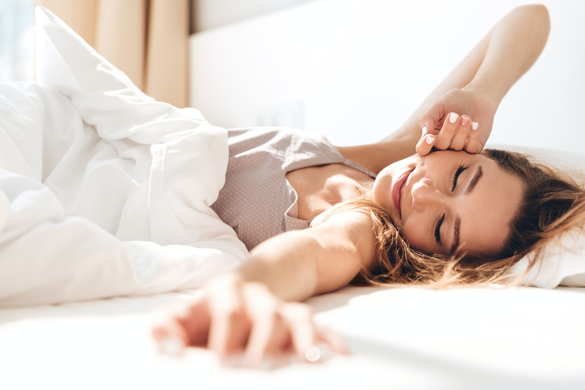 Image of young smiling pretty lady lies in bed indoors. Eyes closed.