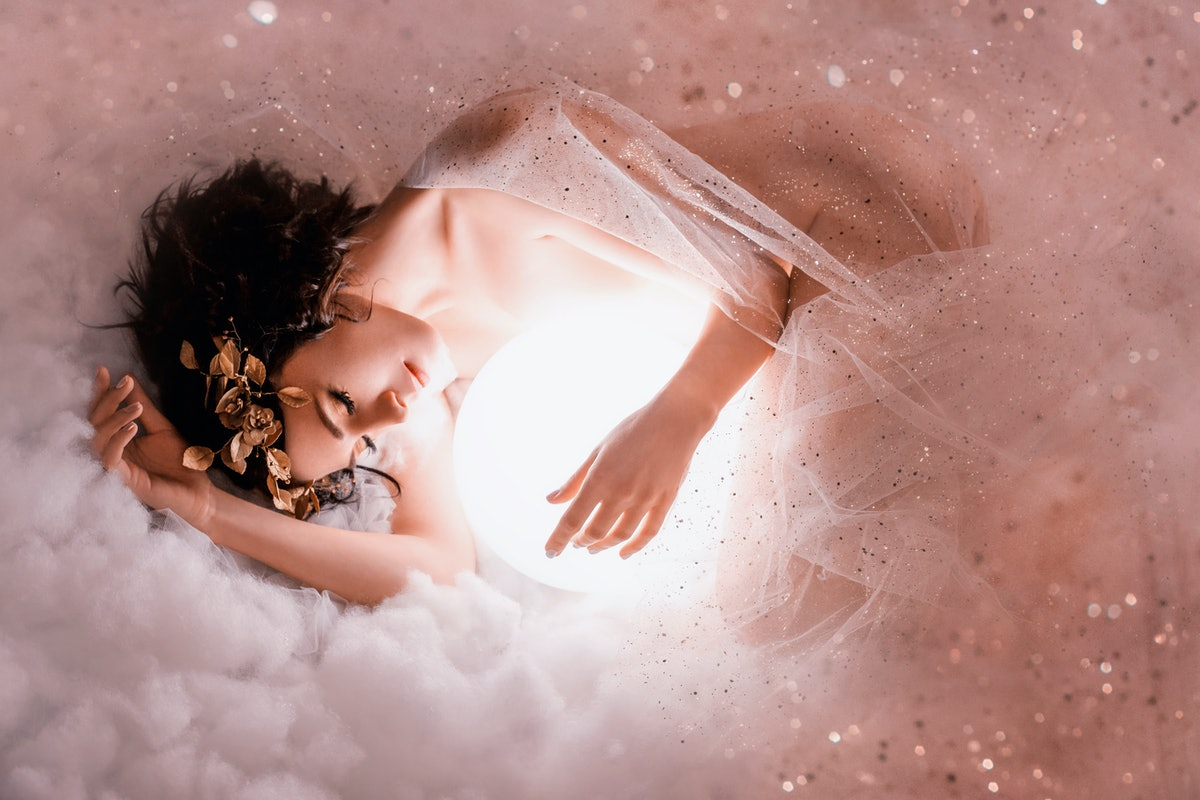 gentle image of angel sleeping to the moon in pink light clouds, naked body of slim girl lying in a mist, covered with glitter sequin, princess of the night with dark hair and a wonderful wreath