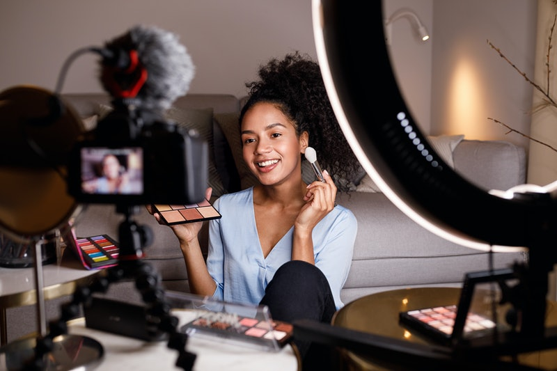 Beauty vlogger making a video tutorial on makeup in living room