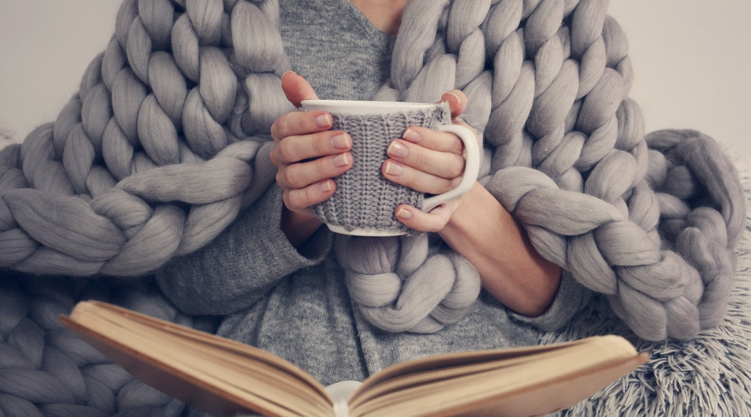 Cozy Woman covered with warm soft merino wool blanket reading a book. Relax, comfort lifestyle.