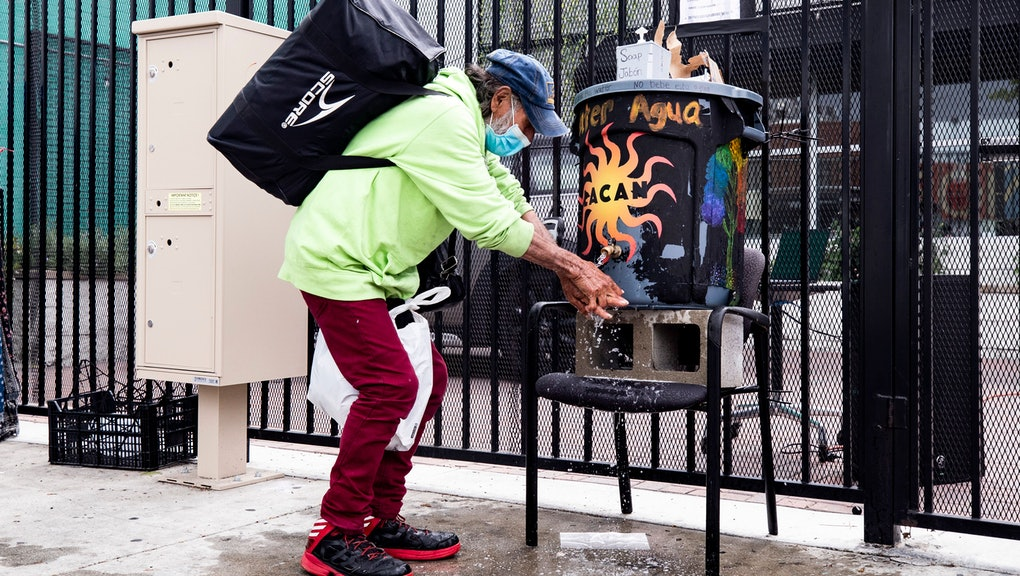 A homeless man washes his hands before receiving a bag of food from the Los Angeles Community Action Network (LA CAN) near Skid Row in Los Angeles, California, USA, 08 April 2020. LA CAN helps people dealing with poverty and homelessness in the Skid Row area. The number of donations have dropped dramatically amid the coronavirus pandemic and LA CAN is struggling to find new sources to help people in need.