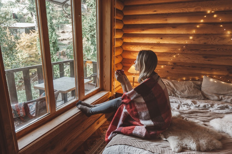 Woman in warm blanket relaxing and drinking morning coffee on cozy bed in log cabin in winter