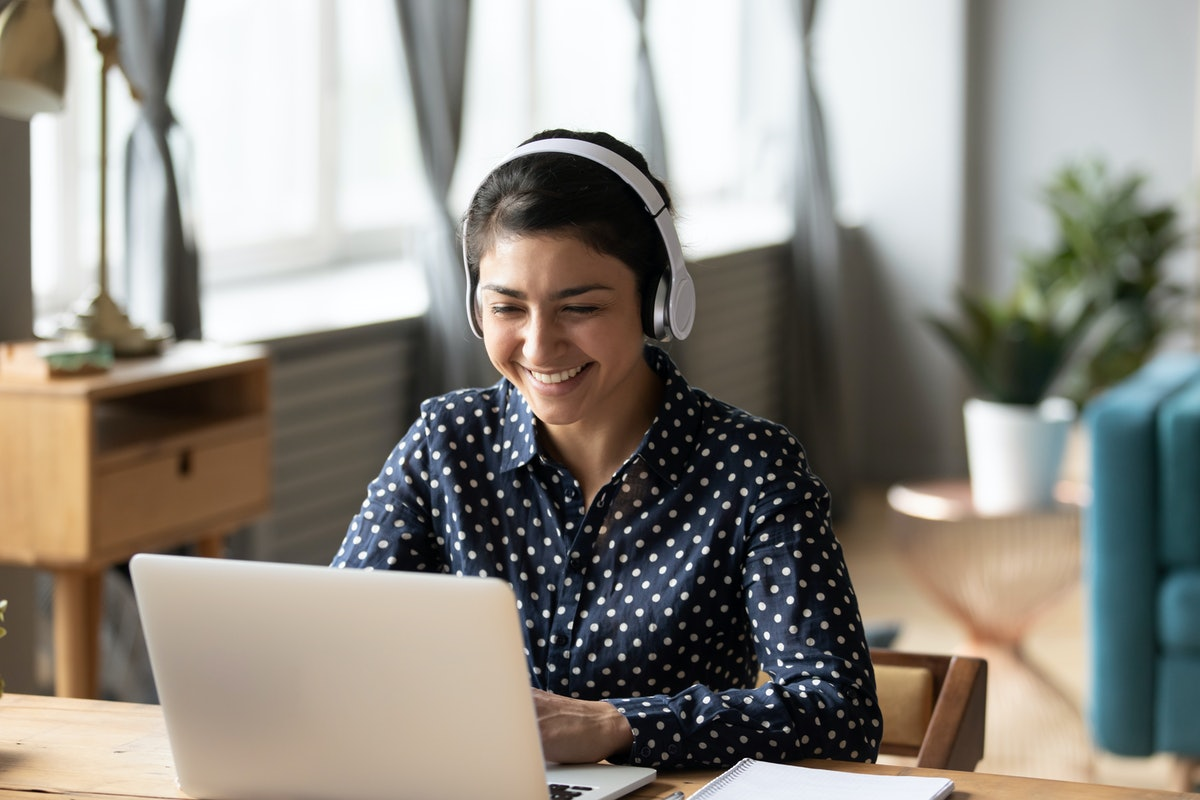 A happy woman wearing headphones and a blue polka dot button down shirt smiles while typing on her laptop.