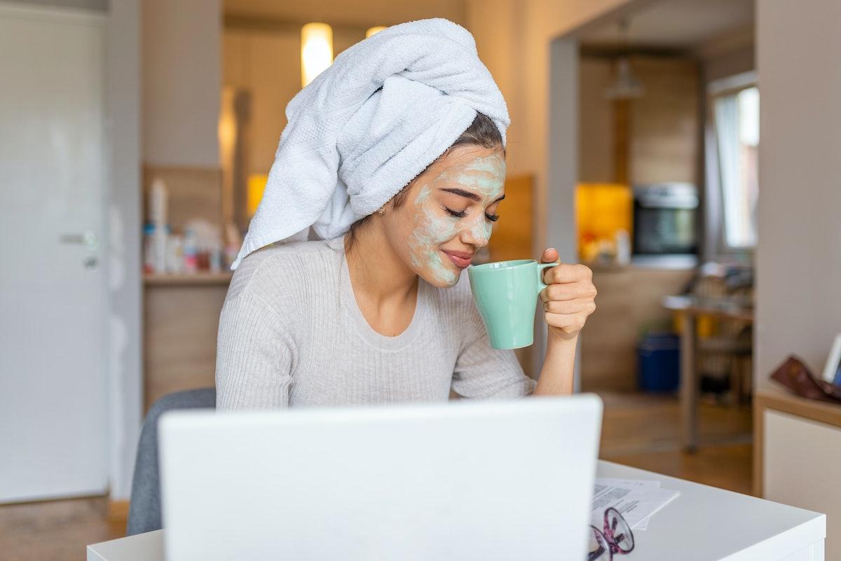Beautiful girl with morning cosmetics mask drinking coffee - tea and reading newspaper. Summer morni...