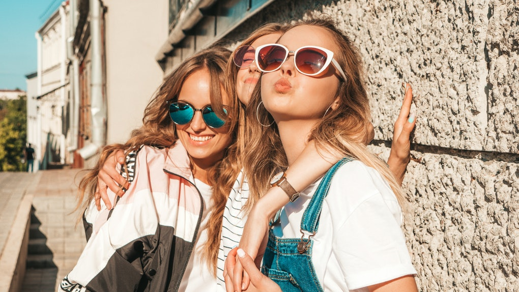 Three happy, trendy women in sunglasses smile in the sunshine while embracing each other.