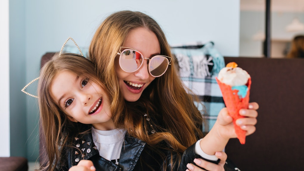 A woman in sunglasses laughs and holds her niece who has cat ears on in an ice cream shop.