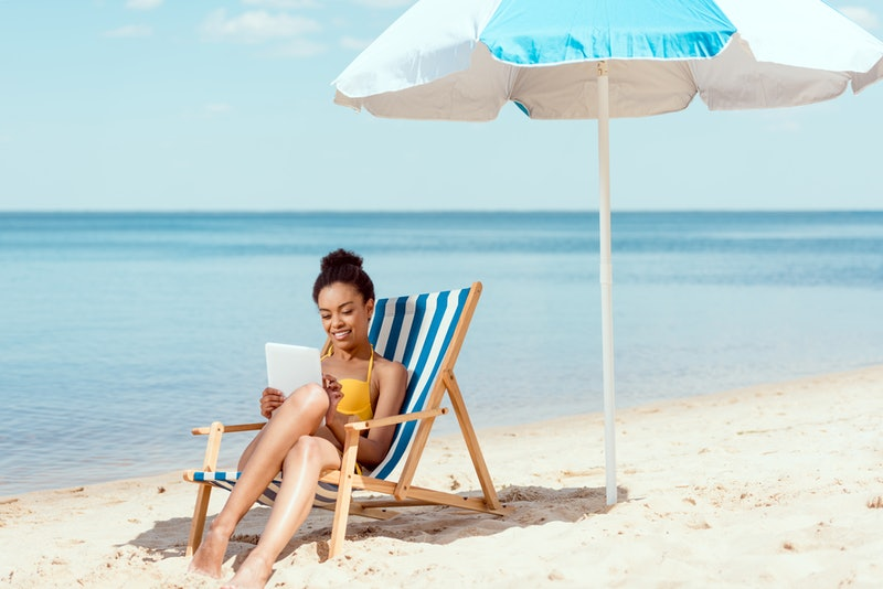 african american woman relaxing on deck chair and using digital tablet under beach umbrella in front of sea