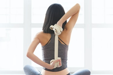 Fitness young woman doing yoga exercise in sportswear with strap near a window in studio, back view....